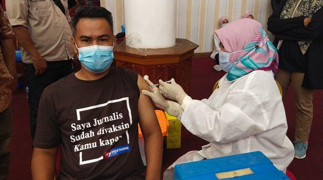 Salah seorang jurnalis, Gusriyono tengah divaksin Covid-19 oleh tenaga kesehatan di Aula Kantor Gubernur Sumbar, Rabu 10 Maret 2021. Foto : Istimewa